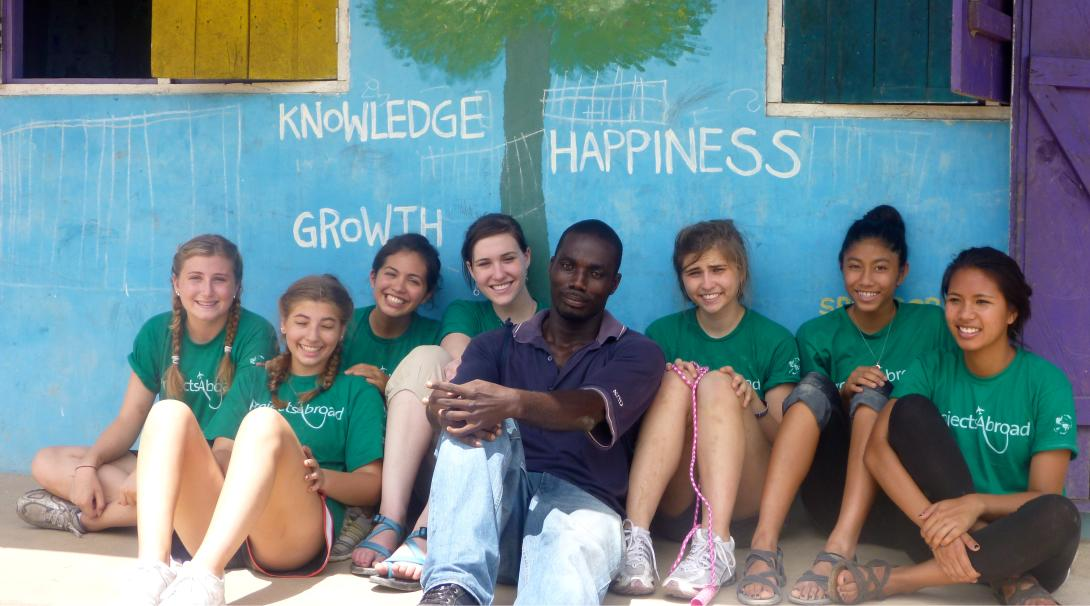 Projects Abroad volunteers sit down for a team photo before continuing their volunteer work with children in Ghana